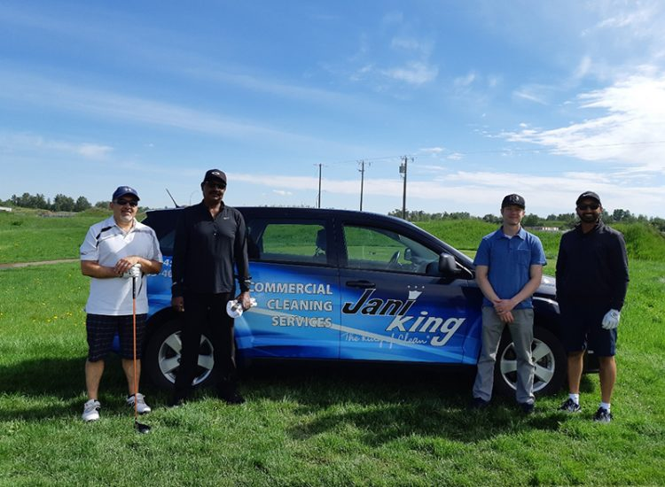 Golfers standing by Jani-King car
