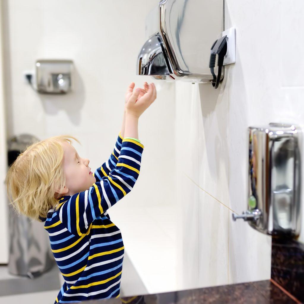 Little boy using air dryer