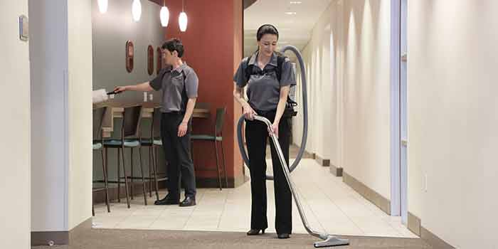 Jani-King Franchisee cleans carpets in commercial hallway